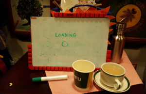 a whiteboard sits upright on a table with the word 'loading' written on it